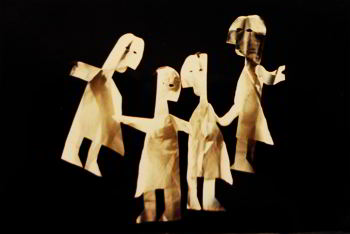 Four life-size paper dolls against a black background