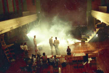long view from balcony of people, props, sets and active smoke machine