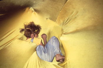 small girl on large raised disc of yellow stretch fabric.
