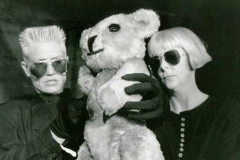 two woman manipulating large teddy-bear