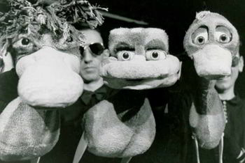 three puppeteers with three large duck puppets