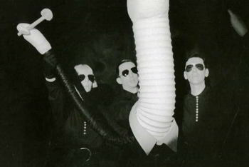three puppeteers operating large phallic puppet wearing a suit