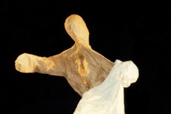 brown paper figure emerges from white cloth covering