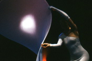 woman in white body-stocking twists large flexible disc into swirling shape