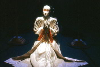 life-size white figure in white ceremonial robe kneels in prayer