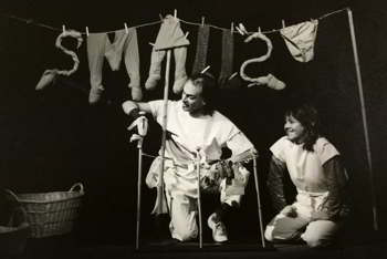 clothesline hung with items spelling the word Smalls behind man and woman with miniature clothesline
